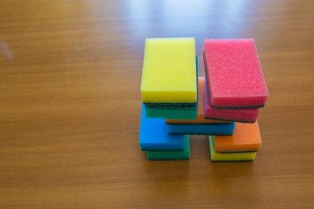 lavar platos: esponjas para lavar platos de colores. Pequeño montón sobre una superficie de madera. Foto de archivo