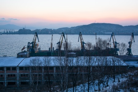 Morning View Of Winter Sea Port. Row Of Cranes Against Sea Vessel Near Pier. Sunrise Above Gulf
