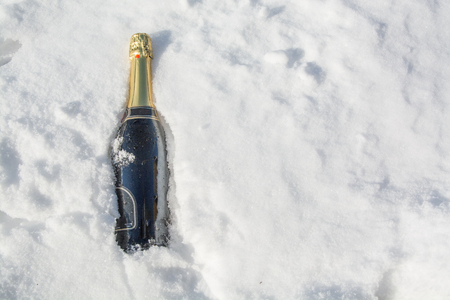 corked: Bottle of champagne is lying in snow. Sunny winter day.
