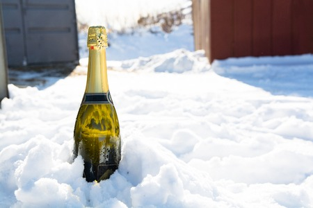 Bottle of champagne is sticking out from snow. Sunny winter day. Stock Photo