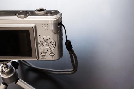 Silver compact digital photo camera. Back view.