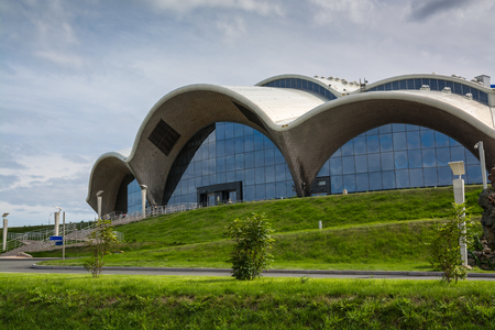 Detail of the facade of a modern building in a curved shape. Futuristic building made from transparent materials.