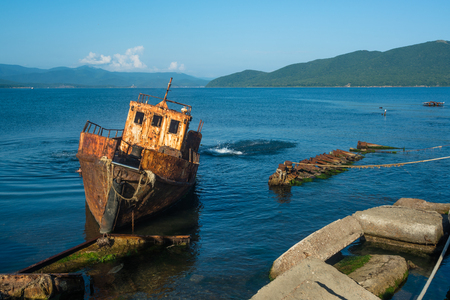 Small abandoned ship near the coast. Tilted rusty nautical longboat near the old pier. Stock Photo