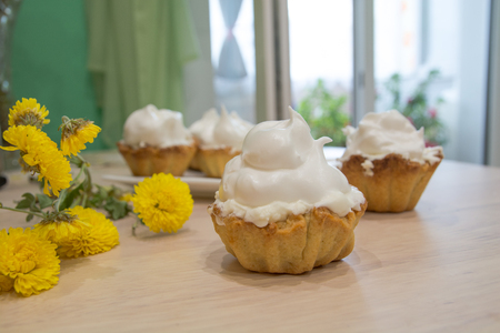 Several cakes basket with whipped cream. Yellow flowers near. Stock Photo