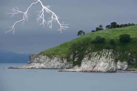 Lightning above green foreland. Seascape. Overcast sky. Stock Photo