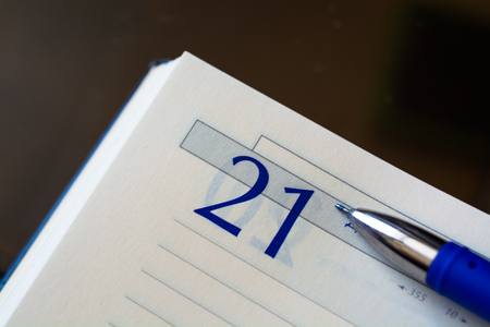 Open diary notebook with a pen. Open on a sheet with date 21. Close up view from above.