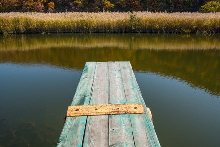 View from the jetty over a calm lake. Small weathered wooden pier. Archivio Fotografico