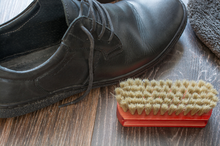 Accessories for shoes cleaning. Mans shoes on wooden surface.