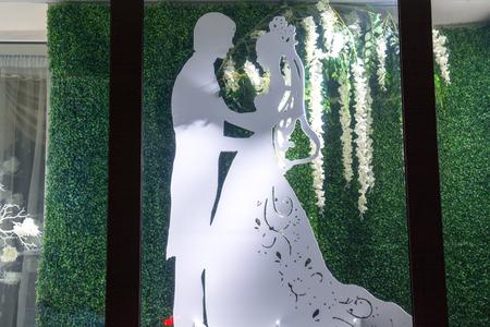 Model of the the couple in illuminated showcase. Night window of shop. Reklamní fotografie