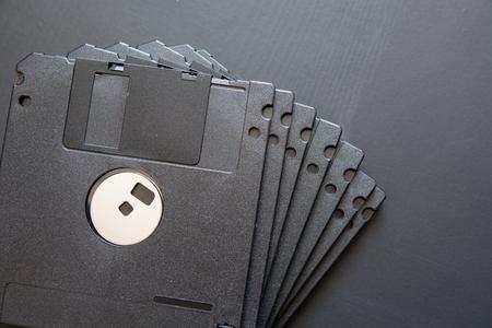 Many black computer diskette on dark background. Old floppy disc.