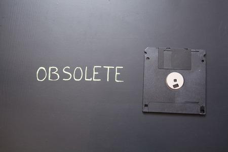 Black computer diskette on dark background. Old floppy disc.
