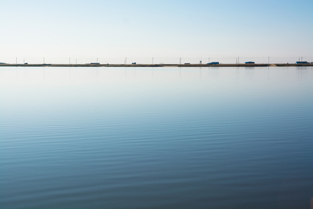 Minimalistic water landscape with road on the lake shore. Alone car moving in the distance. Reklamní fotografie