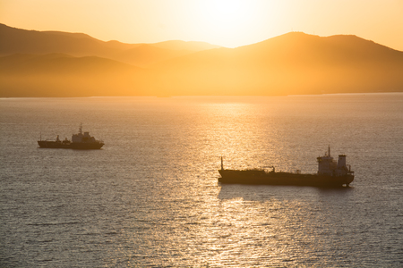 Commercial ships anchored at the bay with golden sunrise in the morning. Sun creates a beautiful golden light on the sea surface.