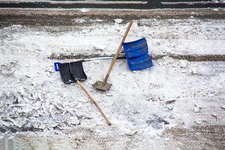 Plastic snow shovel in a snow bank on pavement. Snow removing tools.