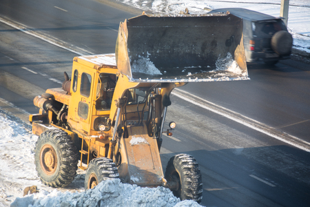 Snow removal vehicle. Tractor clears the way after snowfall.