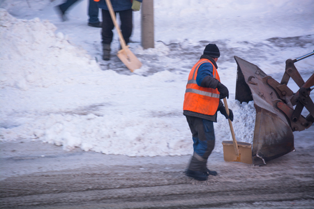 Man removing snow from the road. Cleaning road from snow storm.