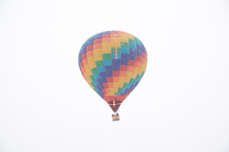 Hot air balloon in the winter season. Snow falling in background of the balloon.