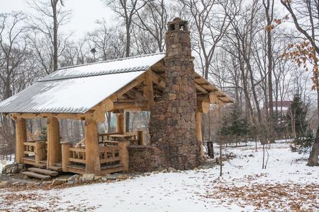 Wooden patio shelter with fireplace. Winter landscape in the park. Reklamní fotografie