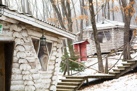 Wooden cabin in snow forest near the stair. Wonderful winter scenery with snow and chalet made from white timber.