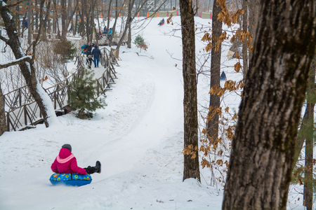 People ride on the snow tubing. Ice slope in the entertainment park. Reklamní fotografie