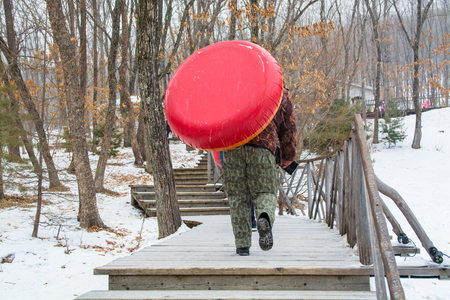 Man pulling up inflatable tubing up stair. Riding on icy hill. Reklamní fotografie