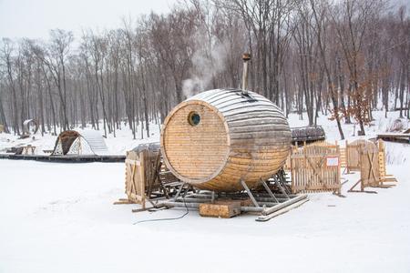 Unusual wooden sauna among snow. Bathhouse in shape of barrel. Snowy winter day.