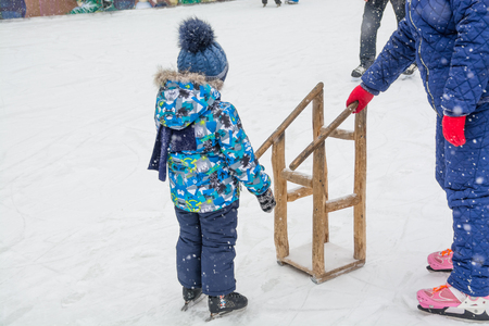 Kid learning to ice skating on a public rink. Support equipment for learning.