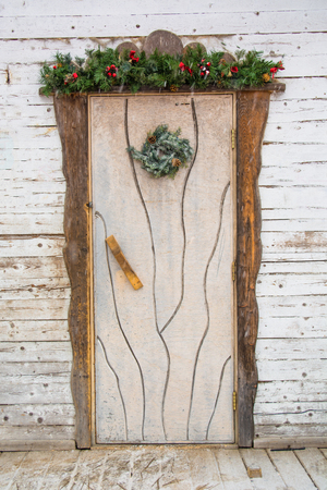 Rustic door with Christmas wreath. Antique white wooden background