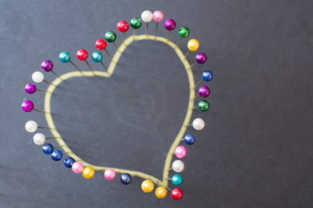 Heart shape from colored pins. Minimalistic image. Reklamní fotografie