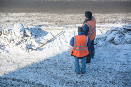 Two road worker near snow heap. Respite of road workers.