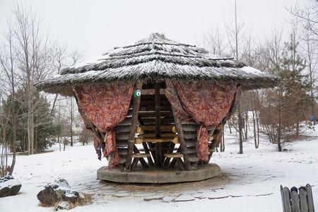 Wooden gazebo in the forest in winter day. Covered gazebo for rest. Reklamní fotografie