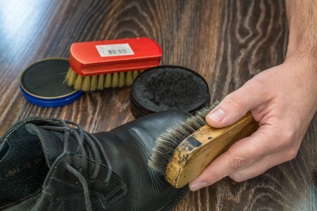 Process of shoes cleaning. Hand, brush and boot closeup. Reklamní fotografie