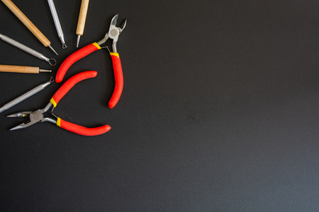 Art tools in a top left corner. On a black background. Small pliers, cutting pliers and stacks.