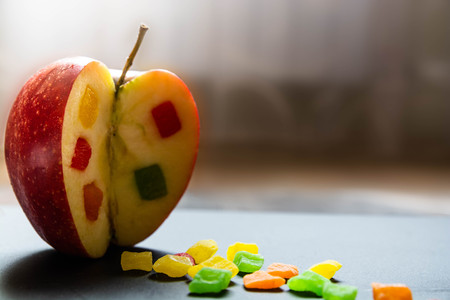 The apple with a candied fruit inside. Close up view on the side of Incised apple. Pieces of candied fruits are around.
