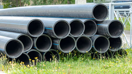 black sewer pipes on the construction site are stacked on top of each other