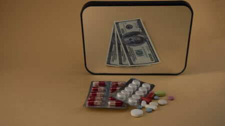 antiviral drugs are reflected in the mirror as money Фото со стока