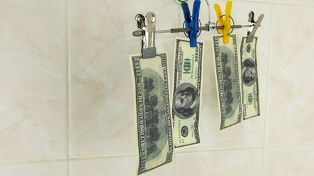 raw dollars hang on a clothes rack Фото со стока