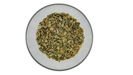 peeled pumpkin seeds in a plate on a white background