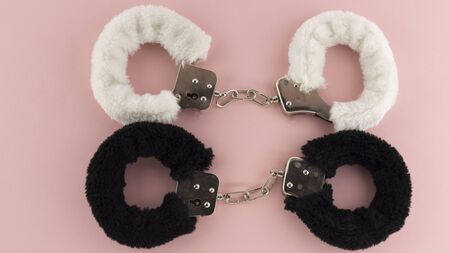 a pair of handcuffs with fluffy pads on a pink background