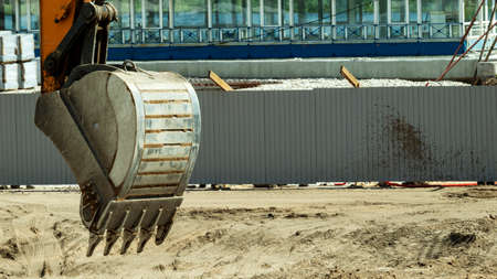 the bucket of a yellow excavator is raised above the ground close up