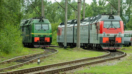 two electric trains standing on the railway tracks in the depot
