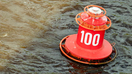the red buoy with the number 100 bobs on the waves