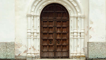 wooden door of the white Church in the medieval style
