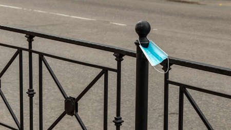 a new medical mask hangs on the road railing