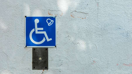 blue sign for the disabled lift on a white wall