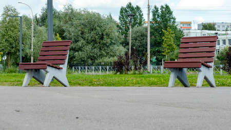two brown wooden benches in a public Park