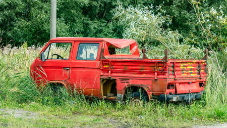 vintage red car after a crash in the grass