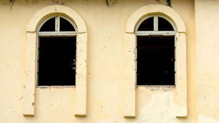 a yellow abandoned building with two damaged Windows Foto de archivo