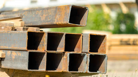 rusty square pipes on the construction site are stacked Foto de archivo