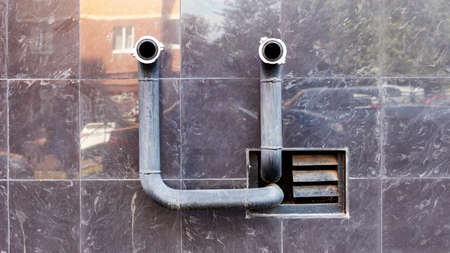 two fire hydrant pipes protrude from the mirrored wall Foto de archivo